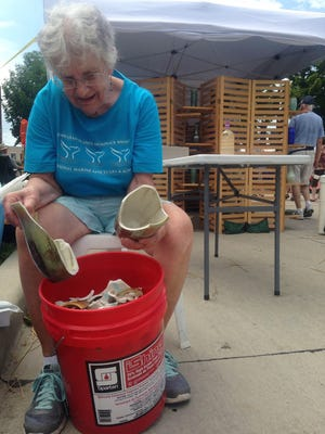 Mary Merrill takes stock of her pottery damaged by storms before the Midsummer Arts Festival on Saturday, July 18. She estimates her losses at $5,000.