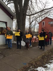 A group of sign-carrying supporters gather to listen to speakers in front of South Dubuque Street cottages Saturday afternoon. About 30 people gathered to show their support for preserving the Civil War-era cottages, and lobby against their destruction.
