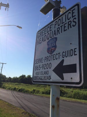 A sign points down a narrow lane leading to the Greece police station at 400 Island Cottage Road.