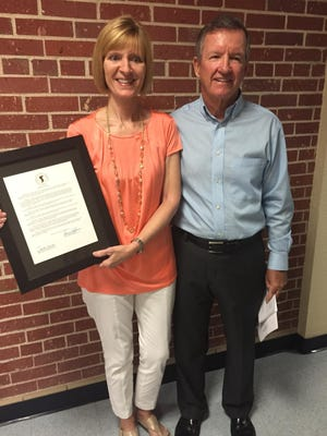 Former Ransom coach Joseph Murphy and his wife, Janet, are pictured with the resolution renaming the middle school's gymnasium in his honor on Tuesday.
