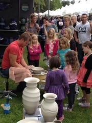 Youngsters checks out Scott Martin at a potters wheel