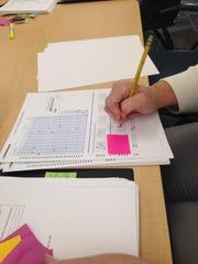 A teacher grades a standardized exam at the University
