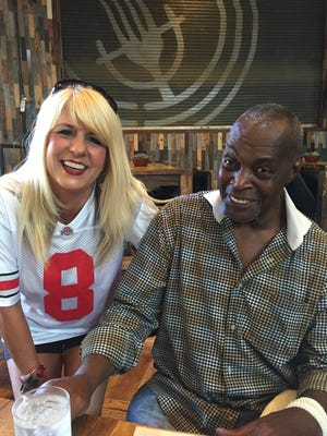 Former Ohio State quarterback Rod Gerald, star of the 1977 Orange Bowl victory over Colorado, with Buckeyes fan Paige King. Gerald credits King for raising funds toward back surgery that will enable him to walk into Ohio Stadium for Saturday's game against Northern Illinois.