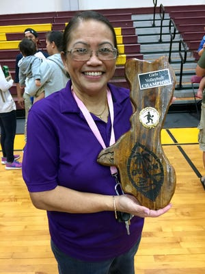 In this file photo, George Washington Geckos head coach Bobbi Quinata holds the IIAAG championship trophy after the Geckos defeated the ND Royals in last year's championship game.