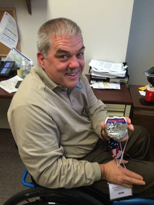 Chris Blaxton shows his medal for completing the Detroit Free Press Marathon, his third. He uses a handcycle to compete.