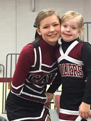 Alayna Scallion, right, and her sister Hannah take a picture before a Crockett Middle basketball game.