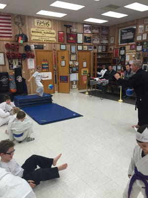 A student at FMK Karate in Binghamton attempts to kick a ball being thrown by owner Frank Kushner, right, while jumping off a mat. The activity teaches coordination, focus and control.