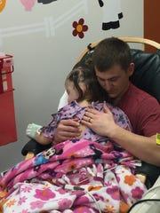 Scarlett Brown, 3, rests in her dad Josh Brown's lap