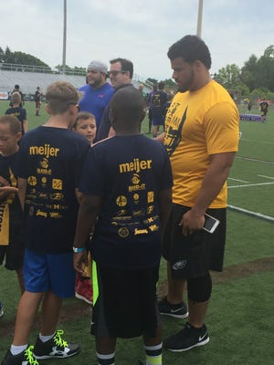 Former player Mike Martin, right, and current player Taco Charlton, back, work with campers Sunday at Martin's youth football camp at Ann Arbor Pioneer.