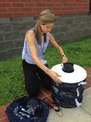 Lara Gaffney, of New Rochelle, sets up a Zika surveillance kit to trap mosquitos in Baltimore.