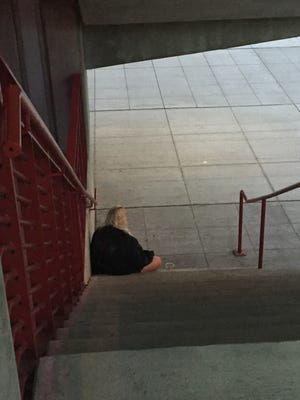 A homeless woman, who said her name was Chloe Kendall, sits on the steps going to U.S. Bank Arena before the Trump rally on Oct. 13.