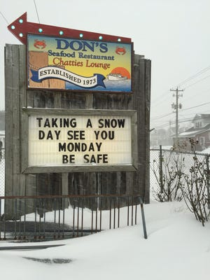 A sign outside of Don's Seafood in Chincoteague, Virginia, announces its closure for the day Saturday, Jan. 17, 2017, due to snow.