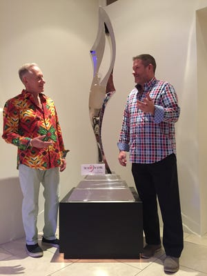 (L to R) Gil Rose, program host, and Chris Ruetz, DAP director of development, share a story about the prized Russell Jacques work of art between them. The piece is a promised future gift to the HeART of Giving Program, from the Rose and Russell collection.