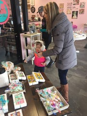 Brooklyn Cunningham, 3, selects a cookie with her mom, Lisa Cunningham of Le Roy, at Jenn's Cookie Creations.