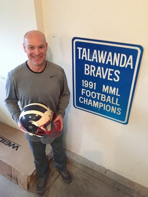 Thad Persinger shares the helmet he wore in Talawanda's upset of Princeton in the 1991 Division I football playoffs. The street sign hangs on a garage wall.
