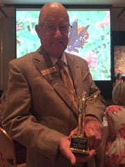 Ophelia Project Chairman Bill Powers displays his Angel on Earth Award for unselfish sacrifice and human service. The butterfly over his shoulder represents the missive of encouraging young girls to use their wings to take flight. Vice Chairwoman Gale Hackshaw (not pictured) also received an Angel on Earth Award.