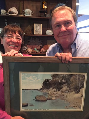Alison Falls presents Kenneth Landon, Catawba Island Historical Society Trustee, with an early print of the beach at Rock Ledge.