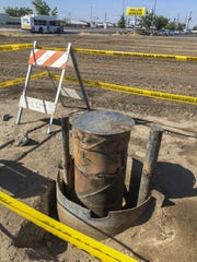A water well casing sticks above ground next to a field