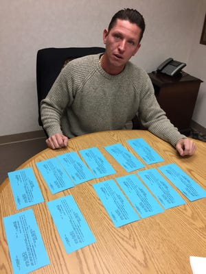 At his lawyer's office on Dec. 13, Donny Barnes of Lake Orion shows appearance slips for the many court dates adjourned by prosecutors, delaying return of his family's bank account.