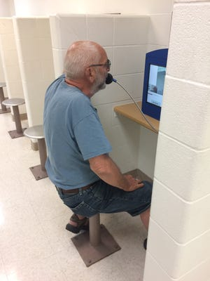Miles Smith conducts a video visitation from a kiosk in the Wayne County Jail.