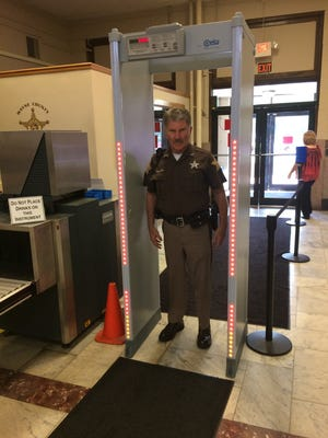 Deputy Mark Stover, a member of the Wayne County Courthouse security team, demonstrates how a new metal detector's lights indicate the presence of metal and its location on a person.