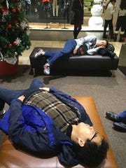 Black Friday shoppers Yuhui Wu and Yi Zhung of College Park, Maryland take a break from shopping at Christiana Mall around 6 a.m.
