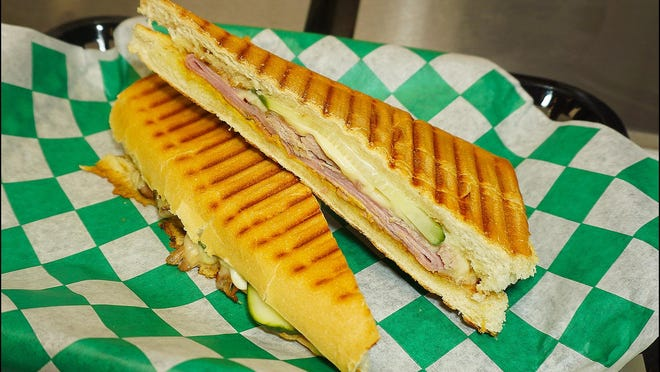 The Cubano sandwich is made with black forest ham, roasted pork, Swiss cheese, homemade dill pickles, and mustard aioli on a grilled baguette.