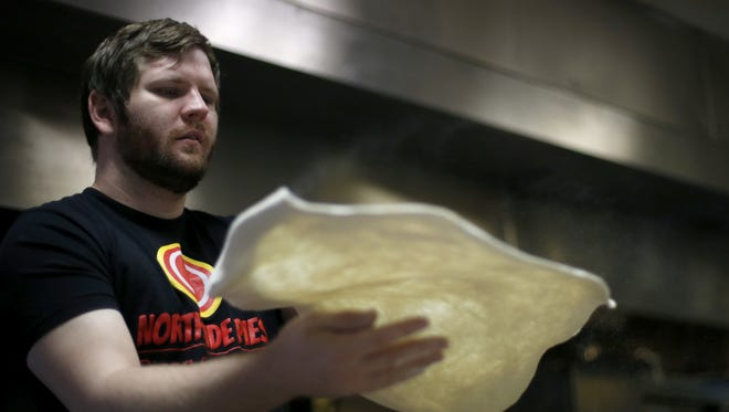 Jeremy Matlow, co-owner of Northside Pies, prepares dough for a pizza at his restaurant.