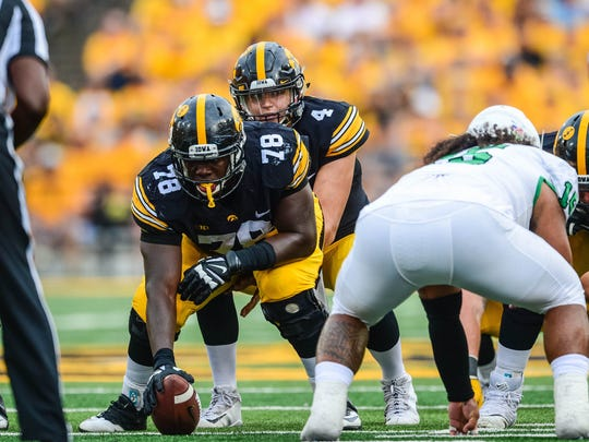 Iowa Hawkeyes quarterback Nathan Stanley (4) looks over offensive lineman James Daniels (78) during the game against the North Texas Mean Green at Kinnick Stadium.
