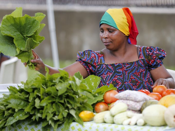 Tanzanian immigrant Evelyne Barampanze assembles her produce for sale during the Global Greens Farmers Market at Lutheran Services in Iowa on Saturday, Aug. 23, 2014, in Des Moines.  The market, launched in June, features fruits and vegetables grown by displaced farmers who have resettled in Iowa.