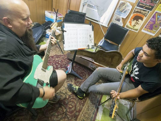 Rod Goelz, left, works with Eli Weary, 14, at the Campbell's Music Services building in York Township. Next week, Goelz will be leading a guitar camp for kids for the first time in York.