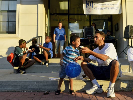 Jeremiah Markline, right, gives his 3-year-old son J'maani a bite of cupcake during National Night Out on Tuesday in the 200 block of East College Street in York city. Various municipalities and police departments in York County teamed up to host National Night Out, an annual, nationwide event designed to strengthen relationships between communities and police.