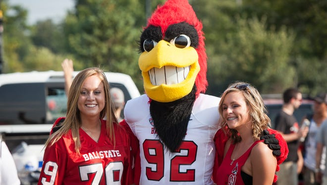 Ball State students Kaitlyn Moss and Kara Boot pose with Charlie Cardinal at the tailgate party for the Ball State University home football game against the Virginia Military Institute in 2015.
