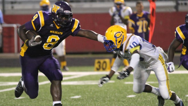 Wossman's Ladarruis Thomas (8) gains yards for the Wildcats as the play the Carroll Bulldogs Friday night in Monroe.