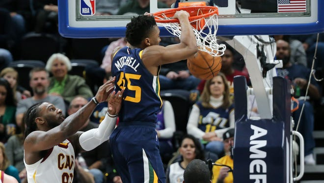 Utah Jazz guard Donovan Mitchell dunks the ball past Cleveland Cavaliers forward Jae Crowder during the first quarter at Vivint Smart Home Arena.