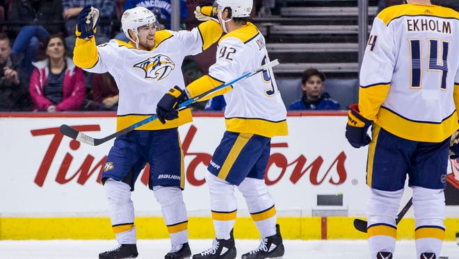 Dec 13, 2017; Vancouver, British Columbia, CAN; Nashville Predators left wing Viktor Arvidsson (33) celebrates with center Ryan Johansen (92) after scoring a goal in the first period against the Vancouver Canucks  at Rogers Arena. Mandatory Credit: Bob Frid-USA TODAY Sports