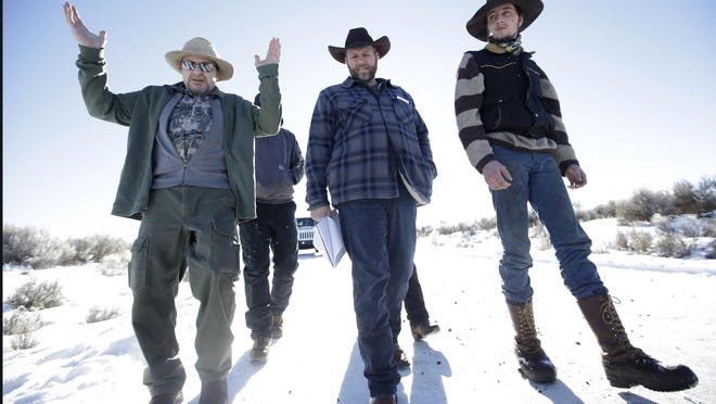 FILE - In this Jan 8, 2016, file photo, Burns resident Steve Atkins, left, talks with Ammon Bundy, center, one of the sons of Nevada rancher Cliven Bundy, following a news conference at Malheur National Wildlife Refuge near Burns, Ore. It has been a month since jury selection began in the trial of the Bundy brothers and 5 others charged in connection with the winter takeover of the national wildlife refuge in southeast Oregon. (AP Photo/Rick Bowmer, file)