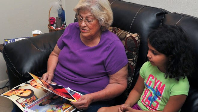 """Sandy Cadena and her granddaughter Bella look at pictures July 19, 2017, of the child's mother, Natasha Cadena, who committed suicide on Independence Day 2017 in Wichita Falls, Texas. Sandy Cadena says her daughter's death is linked to the """"Blue Whale Challenge."""""""