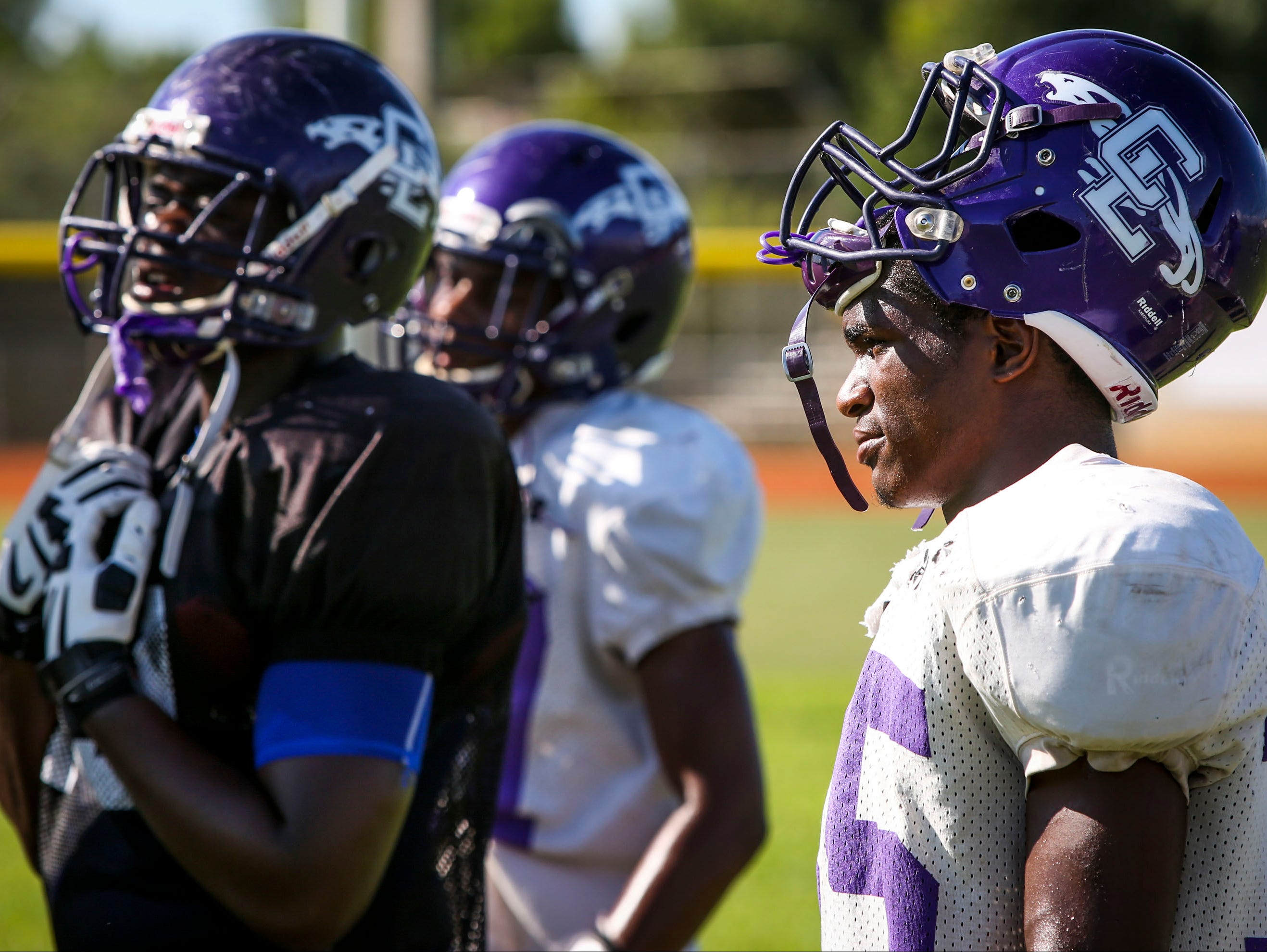 Cliff Moore, running back, for Cypress Lake High School listens to his coach during football practice Wednesday afternoon.