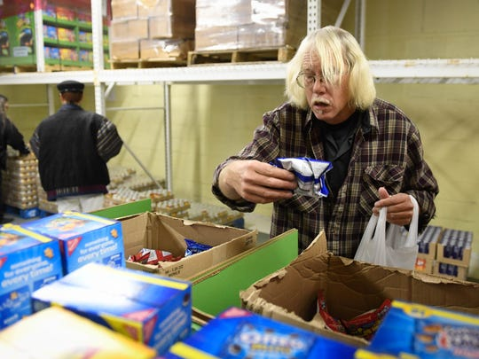 Volunteer Michael Corbett look through boxes of snacks as he fills take home weekend food bags for elementary students Friday, December 2, 2016.