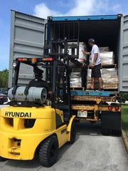 Mixed martial arts star Frank Camacho loads a container with donated supplies to help provide aid to Saipan following Super Typhoon Soudelor.