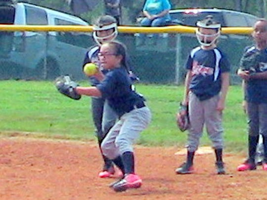 A player puts some energy into her throwing arm.