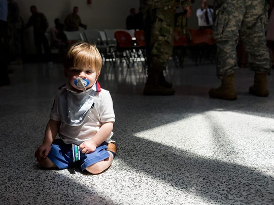 14 month old Dyer Ford, son of Capt. Robert Ford and Jessica Ford, sits on the floor at the close of the deployment ceremony at the Smyrna Readiness Center.