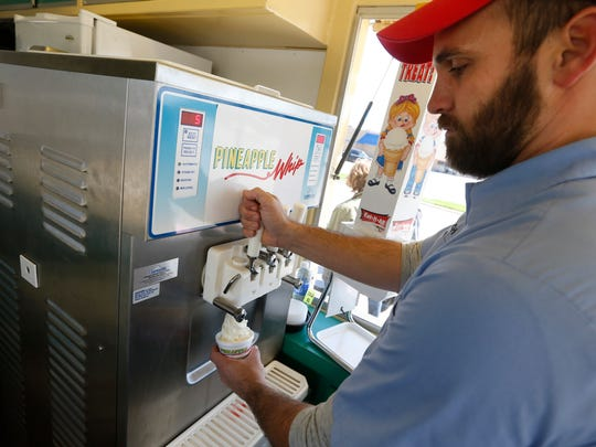 Zach Fortner pours a Pineapple Whip during their first day of the season on Friday, Mar. 25, 2016 at 3850 S Campbell Ave.