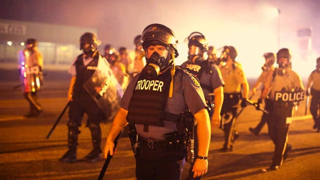 Police advance through a cloud of tear gas toward demonstrators protesting the killing of teenager Michael Brown on August 17, 2014 in Ferguson, Missouri.