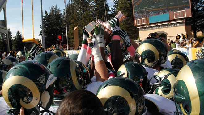 The Colorado State Rams celebrate with the Bronze Boot Trophy after the Border War with the Wyoming Cowboys at War Memorial Stadium in 2013 The Rams defeated the Cowboys 52-22.