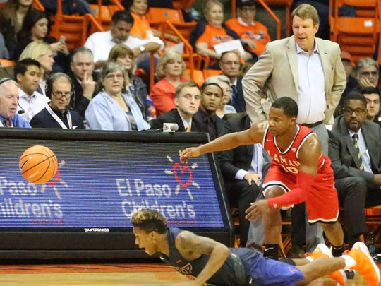 UTEP's Evan Gilyard, bottom, dives for a loose ball as UTEP head basketball coach Tim Floyd watches.