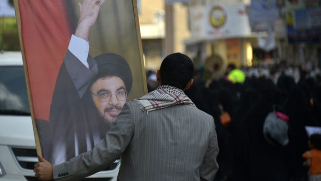 A Yemeni Shiite man holds a picture of Lebanese Hezbollah leader Hassan Nasrallah during a protest against a possible military action against Syria, in Sana?a, Yemen, 30 August 2013.