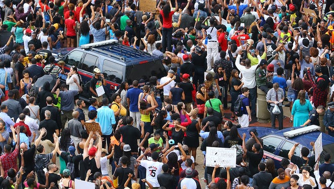Protesters rally for Mike Brown and Ferguson filling the side walks and street outside the CNN Center on Monday, Aug.18, 2014, in Atlanta.  (AP Photo/Atlanta Journal-Constitution, Curtis Compton)   ORG XMIT: GAATJ105