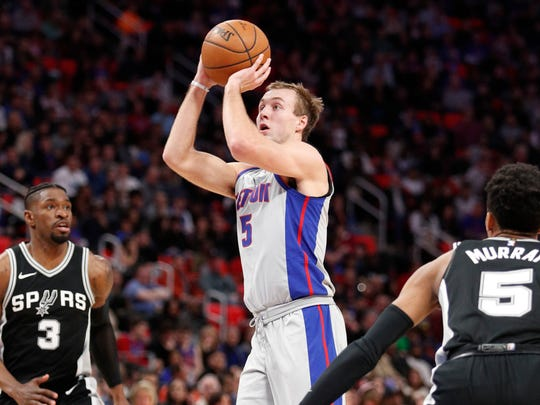 Pistons guard Luke Kennard (5) takes a shot in between Spurs guard Brandon Paul (3) and guard Dejounte Murray (5) during the second quarter on Saturday, Dec. 30, 2017, at Little Caesars Arena.